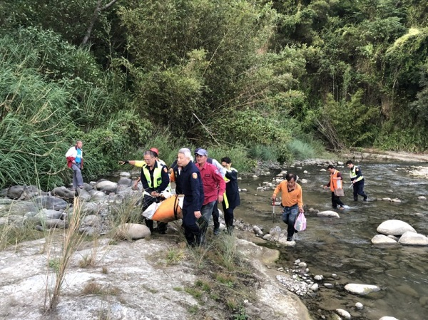 救难人员从河床将遗体运出(记者郑名翔翻摄)